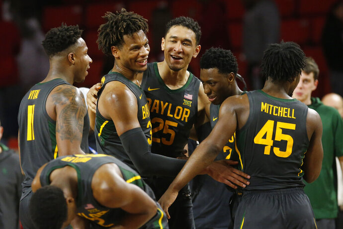 Baylor's Mark Vital, Freddie Gillespie, Tristan Clark, Devonte Bandoo and Davion Mitchell, from left, celebrate after Baylor defeated Oklahoma 65-54 in an NCAA college basketball game in Norman, Okla., Tuesday, Feb. 18, 2020. (AP Photo/Sue Ogrocki)