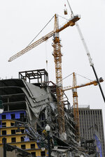 Workers in a bucket, top, begin the process of planting explosive charges on two unstable cranes at the Hard Rock Hotel, which underwent a partial, major collapse on Saturday, Oct. 12, in New Orleans, viewed on Thursday, Oct. 17, 2019. Authorities say explosives will be strategically placed on the two unstable construction cranes in hopes of bringing them down with a series of small controlled blasts ahead of approaching tropical weather. Officials hope to bring the towers down Friday without damaging nearby businesses and historic buildings in and around the nearby French Quarter. (AP Photo/Gerald Herbert)