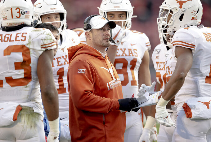 Texas head coach Tom Herman looks at the replay of a touchdown catch by wide receiver Brennan Eagles (13) against Iowa State during an NCAA college football game on Saturday, Nov. 16, 2019, in Ames, Iowa. (Nick Wagner/Austin American-Statesman via AP)