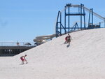 This Monday,  June 8, 2020 photo shows beachgoers playing on a large sand dune in North Wildwood, N.J. On June 6, 2020, the New Jersey Department of Environmental Protection said North Wildwood had demolished dunes and wetlands, built a sea wall and added buildings to a pier without required permits or review by the agency, which may make the city tear the work it did, and restore the area to its natural condition. (AP Photo/Wayne Parry)