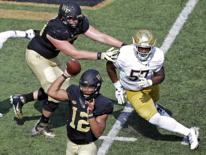 FILE - In this Sept. 22, 2018, file photo, Wake Forest's Jamie Newman (12) looks to pass as Notre Dame's Jayson Ademilola (57) pressures in the second half of an NCAA college football game in Winston-Salem, N.C. Wake Forest will start Newman at quarterback this week against No. 22 North Carolina State. He replaces Sam Hartman, a freshman who started the first nine games before suffering a season-ending leg injury late in last week's 41-24 loss to No. 13 Syracuse. (AP Photo/Chuck Burton, File)