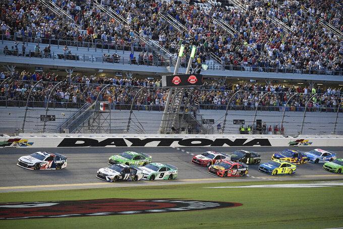 William Byron (24) and Denny Hamlin (11) lead the field to start a NASCAR Cup Series auto race at Daytona International Speedway, Saturday, Aug. 28, 2021, in Daytona Beach, Fla. (AP Photo/Phelan M. Ebenhack)