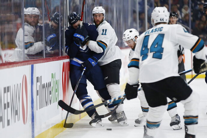 San Jose Sharks' Stefan Noesen (11) draws a high-sticking penalty with this check on Winnipeg Jets' Tucker Poolman (3) during the second period of an NHL hockey game Friday, Feb. 14, 2020, in Winnipeg, Manitoba. (John Woods/The Canadian Press via AP)