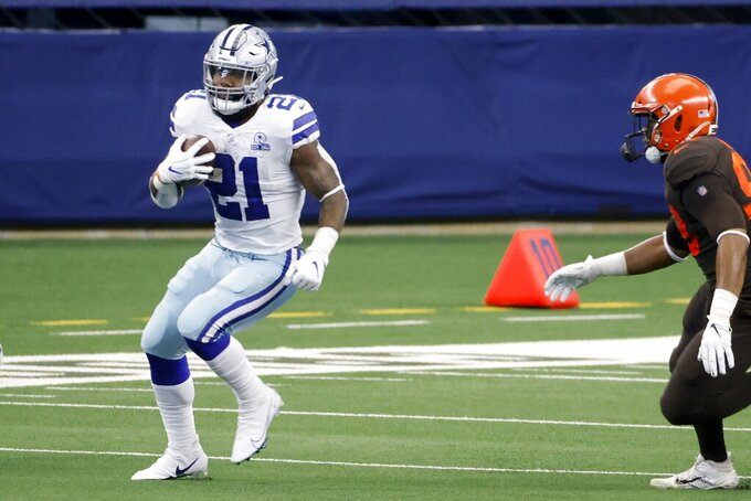 Dallas Cowboys running back Ezekiel Elliott (21) runs the ball under pressure from Cleveland Browns defenders in the first half of an NFL football game in Arlington, Texas, Sunday, Oct. 4, 2020. (AP Photo/Ron Jenkins)