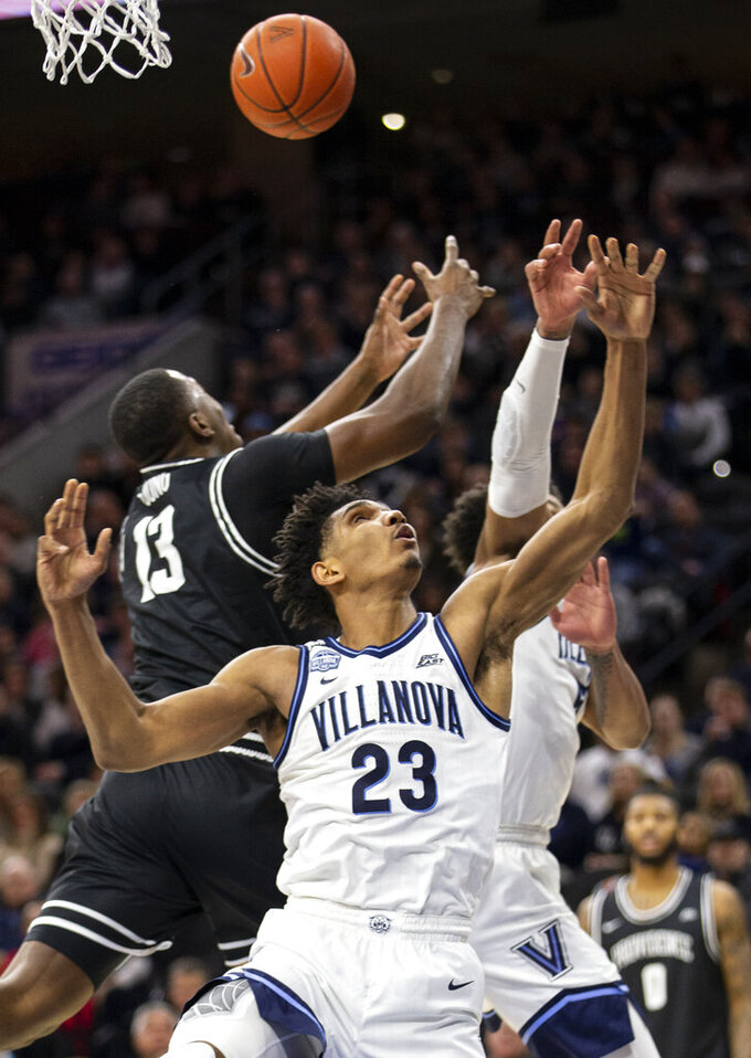 Villanova forward Jermaine Samuels (23) and Providence forward Kalif Young (13) reach for a rebound during the second half of an NCAA college basketball game, Saturday, Feb. 29, 2020, in Philadelphia. Providence won 58-54. (AP Photo/Laurence Kesterson)