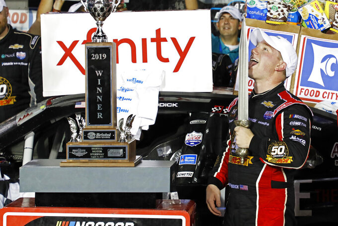 Tyler Reddick licks the sword after winning an NASCAR Xfinity Series auto race on Friday, Aug. 16, 2019, in Bristol, Tenn. (AP Photo/Wade Payne)