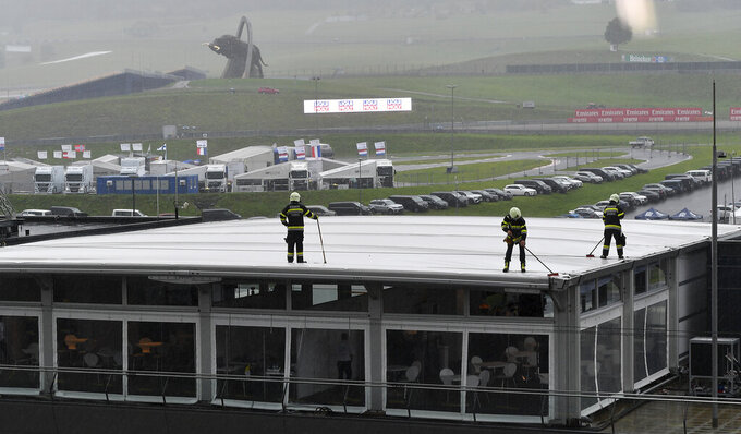 Firefighters work to clear rain from the roof during heavy rain before the morning scheduled third practice session for the Styrian Formula One Grand Prix at the Red Bull Ring racetrack in Spielberg, Austria, Saturday, July 11, 2020. The Styrian F1 Grand Prix will be held on Sunday. (Joe Klamar/Pool via AP)