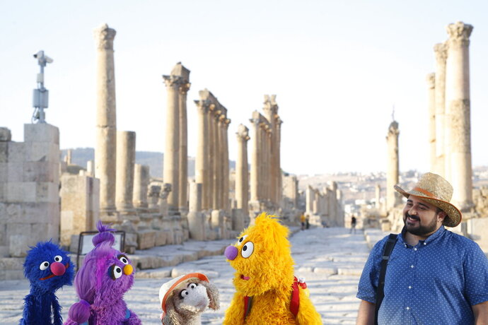 This image released by Sesame Workshop shows, from left, Grover, Basma, Ma'zooza and Jad with Rami Delshad, who portrays Hadi in
