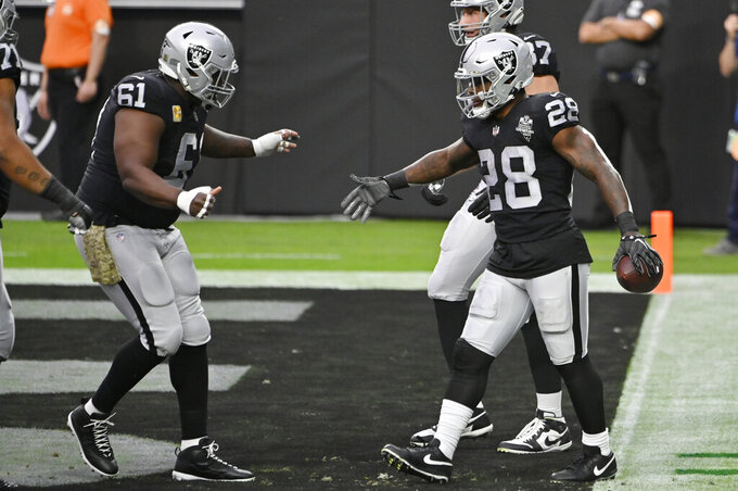 Las Vegas Raiders center Rodney Hudson (61) celebrates after running back Josh Jacobs (28) scored a touchdown against the Denver Broncos during the first half of an NFL football game, Sunday, Nov. 15, 2020, in Las Vegas. (AP Photo/David Becker)