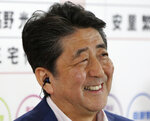 Japan's Prime Minister Shinzo Abe, leader of the Liberal Democratic Party, smiles during a TV interview at the party headquarters in Tokyo, Sunday, July 21, 2019. Exit polls have showed Prime Minister Shinzo Abe's ruling coalition is certain to keep the majority of 124 seats contested in Sunday's upper house election, and could go even closer to the super-majority, the key line needed to propose a constitutional revision if joined by supporters from smaller parties. (AP Photo/Koji Sasahara)