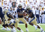 Navy quarterback Malcolm Perry hands off to Nelson Smith in the first quarter of an NCAA college football game against Holy Cross, Saturday, Aug. 31, 2019, in Annapolis, Md. (Paul W. Gillespie/Capital Gazette via AP)