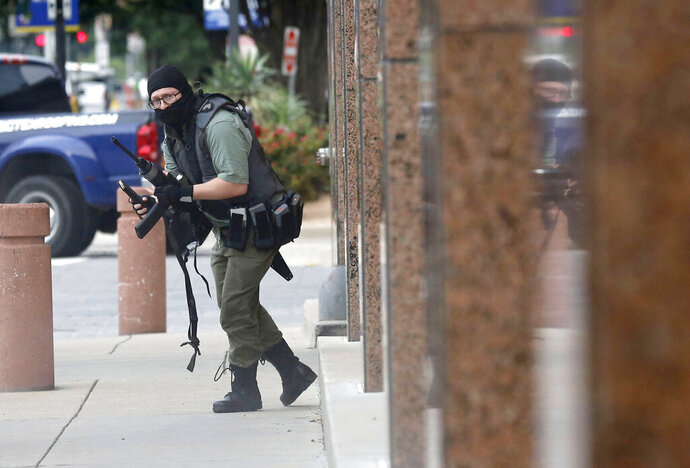 An armed shooter stands near the Earle Cabell Federal Building Monday, June 17, 2019, in downtown Dallas. The shooter was hit and injured in an exchange of gunfire with federal officers outside the courthouse.  (Tom Fox/The Dallas Morning News) MANDATORY CREDIT, NO SALES, MAGS OUT, TV OUT, INTERNET USE BY AP MEMBERS ONLY