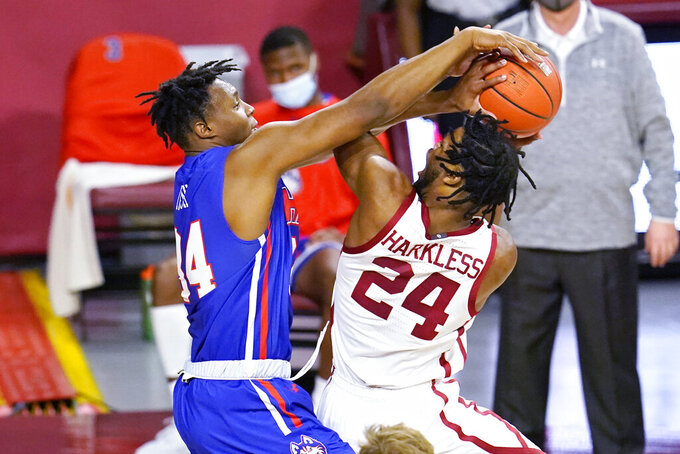 Houston Baptist center Zach Iyeyemi, left, blocks a shot by Oklahoma guard Elijah Harkless (24) in the first half of an NCAA college basketball game Saturday, Dec. 19, 2020, in Norman, Okla. (AP Photo/Sue Ogrocki)