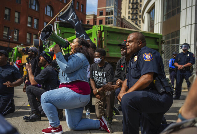 Protest organizer Alyssa Bates, left, kneels beside Grand Rapids police Chief Eric Payne during a protest in downtown Grand Rapids, Mich., Wednesday, June 3, 2020, prompted by the death of George Floyd. (Anntaninna Biondo/The Grand Rapids Press via AP)