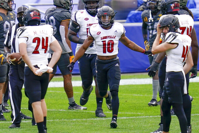 Louisville running back Javian Hawkins (10) celebrates with teammates after making a long touchdown run against Pittsburgh during the first half of an NCAA college football game, Saturday, Sept. 26, 2020, in Pittsburgh. (AP Photo/Keith Srakocic)