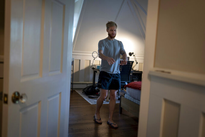 Brad Snyder leaves his wife's office after serving her a tea at their home in Princeton, N.J., on Wednesday, Aug. 4, 2021. A Navy explosives expert, Snyder stepped on hidden mine in Afghanistan in 2011 as he moved to help a group of Afghan commandos badly injured by another blast. In moments he went from thinking he was dead, to relief that he was alive, to confusion as he stood up with blood pouring from his face. (AP Photo/Emilio Morenatti)