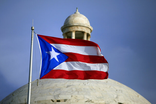 FILE - In this July 29, 2015 file photo, the Puerto Rican flag flies in front of Puerto Rico's Capitol as in San Juan, Puerto Rico. A senior Puerto Ricon official said Tuesday, Feb. 11, 2020, that the island's government has lost more than $2.6 million after falling for an email phishing scam. (AP Photo/Ricardo Arduengo, File)