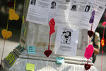 Posters with photographs of victims are posted on a plinth during a tribute for murdered women, in the Alameda park of Mexico City, Saturday, Aug. 24, 2019. A small group of women constructed a memorial made of hand-knit hearts. The knit-in on came on the heels of rowdy protests sparked by outrage over bungled investigations into alleged rapes of teenagers by local policemen. (AP Photo/Ginnette Riquelme)