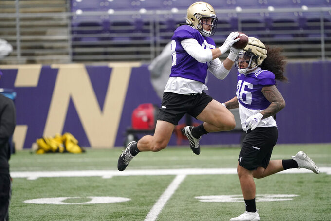 Washington linebacker Jackson Sirmon leaps to make a catch during NCAA college football practice, Friday, Oct. 16, 2020, in Seattle. (AP Photo/Ted S. Warren)
