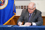 """FILE - In this July 23, 2020, file photo, Gov. Tim Walz signed into law a sweeping package of police accountability measures in St. Paul, Minn., making Minnesota the latest state to adopt changes to law enforcement, including a ban on neck restraints, in the wake of George Floyd's death. The bill, passed by the Legislature earlier this week, also bans chokeholds and fear-based or """"warrior-style"""" training, which critics say promotes excessive force. (Glen Stubbe/Star Tribune via AP, File)"""