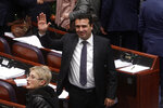 Macedonian Prime Minister Zoran Zaev waves to the media gallery after the parliament voted in favor of the constitutional changes, in Macedonian Parliament in the capital Skopje, Friday, Jan. 11, 2019. Macedonia has fulfilled its part of a deal that will pave its way to NATO membership and normalize relations with neighboring Greece, after lawmakers approved constitutional changes that will rename the country North Macedonia. (AP Photo/Boris Grdanoski)