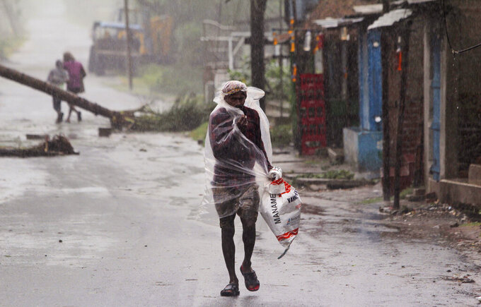 A man covers himself with a plastic sheet and walks in the rain ahead of Cyclone Amphan landfall, at Bhadrak district, in the eastern Indian state of Orissa, Wednesday, May 20, 2020. A strong cyclone blew heavy rains and strong winds into coastal India and Bangladesh on Wednesday after more than 2.6 million people were moved to shelters in a frantic evacuation made more challenging by coronavirus. (AP Photo)