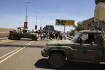 Demonstrators walk past army vehicles protecting the entrance to a rally near the military headquarters in Khartoum, Sudan, Monday, April 15, 2019. The Sudanese protest movement on Monday welcomed the