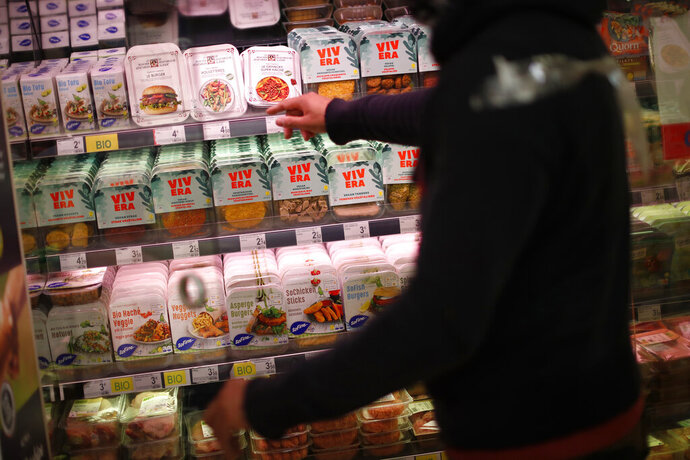 A store clerk shows plant based products at a supermarket chain in Brussels, Friday, Oct. 23, 2020. European lawmakers rejected Friday proposals that could have prevented plant-based products without meat from being labeled sausages or burgers. Following the votes on agricultural products at the European Parliament, the so-called veggie burgers, soy steaks and vegan sausages can continue to be sold as such in restaurants and shops across the union. (AP Photo/Francisco Seco)