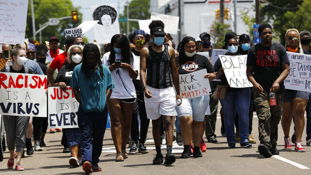 Marchers wave signs and shout slogans during a protest over the death of George Floyd, Monday, June 1, 2020, in Jackson, Miss. Floyd died after being restrained by Minneapolis police officers. Protesters gathered at the Capitol and marched through downtown Jackson voicing their displeasure with the current status of race in America. (AP Photo/Rogelio V. Solis)