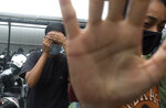 American graphic designer Kristen Antoinette Gray, left, covers her face as her partner Saundra Michelle Alexander tries to covers with her hand as they walked from the local immigration, in Denpasar, Bali, Indonesia on Wednesday, Jan. 20, 2021. Gray, who arrived in Bali in January 2020 and wound up staying through the coronavirus pandemic, is being deported from the Indonesian resort island over her viral tweets that celebrated it as a low-cost, queer-friendly place for foreigners to live. (AP Photo/Firdia Lisnawati)