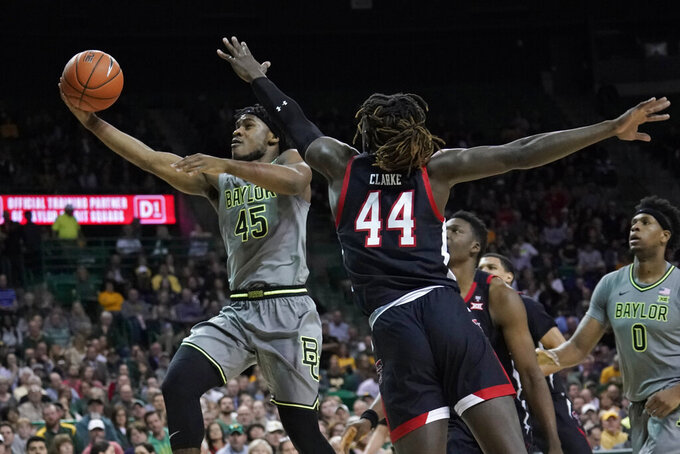 Baylor's Davion Mitchell (45) drives past Texas Tech's Chris Clarke (44) during the first half of an NCAA college basketball game in Waco, Texas, Monday, March 2, 2020. (AP Photo/Chuck Burton)