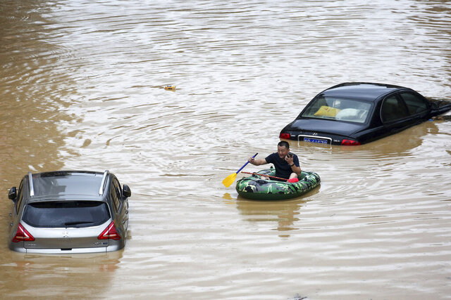 In this photo released by Xinhua News Agency, a man paddles with an inflatable boat past submerged cars during a flood in Rongshui County in southern China's Guangxi Zhuang Autonomous Region, Saturday, July 11, 2020. Vice Minister of Emergency Management Zheng Guoguang told reporters Monday, July 13, 2020 that the Yangtze River and parts of its watershed have seen the second highest rainfall since 1961 over the past six months. (Long Linzhi/Xinhua via AP)