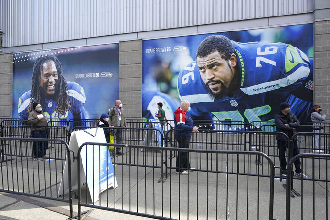 People line up in front of photos of Seattle Seahawks players Shaquill Griffin and Duane Brown, Saturday, March 13, 2021, as they wait to get the first dose of the Pfizer COVID-19 vaccine on the first day of operations at a mass vaccination site at the Lumen Field Events Center in Seattle, which adjoins the field where the NFL football Seahawks and the MLS soccer Seattle Sounders play their games. The site, which is the largest civilian-run vaccination site in the country, will operate only a few days a week until city and county officials can get more doses of the vaccine. (AP Photo/Ted S. Warren)