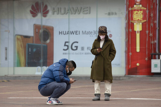 In this Sunday, March 8, 2020, photo, residents wearing masks look at their smartphones near an advertisement for 5G smartphones from Chinese tech giant Huawei in Beijing. Factories in China, struggling to reopen after the coronavirus shut down the economy, face a new threat from U.S. anti-disease controls that might disrupt the flow of microchips and other components they need. For most people, the new coronavirus causes only mild or moderate symptoms. For some it can cause more severe illness. (AP Photo/Ng Han Guan)