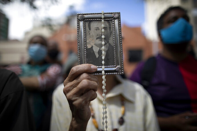 A devotee holds up a framed image of the late Dr. Jose Gregorio Hernandez outside La Candelaria church where his remains are interred, in Caracas, Venezuela, Monday, Oct. 26, 2020. The remains of Hernandez, popularly known as the