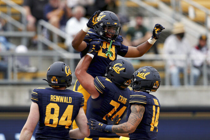 California running back Damien Moore (28) is congratulated by teammates after scoring a touchdown against Sacramento State during the first half of an NCAA college football game on Saturday, Sept. 18, 2021, in Berkeley, Calif. (AP Photo/Jed Jacobsohn)