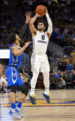 Marquette guard Markus Howard, right, takes a jump shot against Creighton during the first half of an NCAA college basketball game Sunday, March 3, 2019, in Milwaukee. (AP Photo/Darren Hauck)