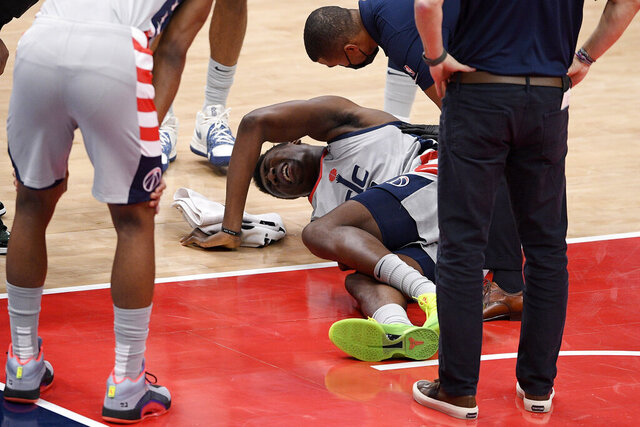 Washington Wizards center Thomas Bryant, center, lies injured on the court during the first half of an NBA basketball game against the Miami Heat, Saturday, Jan. 9, 2021, in Washington. (AP Photo/Nick Wass)