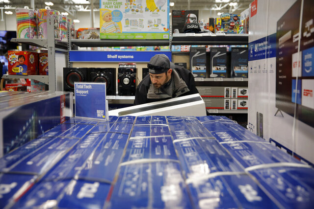FILE - In this Nov. 26, 2019, file photo Nick Bierman looks at televisions while shopping ahead of Black Friday at a Best Buy in Henderson, Nev. Holiday shopping doesn't end with Christmas. Bargain hunters can take advantage of fatter discounts on clothing, home decor and other items between Christmas and well into January. (AP Photo/John Locher, File)