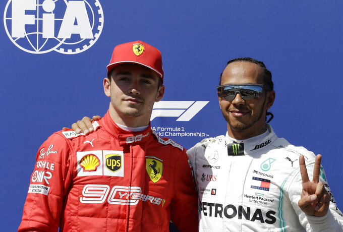 Mercedes driver Lewis Hamilton of Britain, right, who earned pole position, and Ferrari driver Charles Leclerc of Monaco, who came in third, posing for photos after the qualifying session at the Paul Ricard racetrack in Le Castellet, southern France, Saturday, June 22, 2019. The French Formula One Grand Prix will be held on Sunday. (AP Photo/Claude Paris)