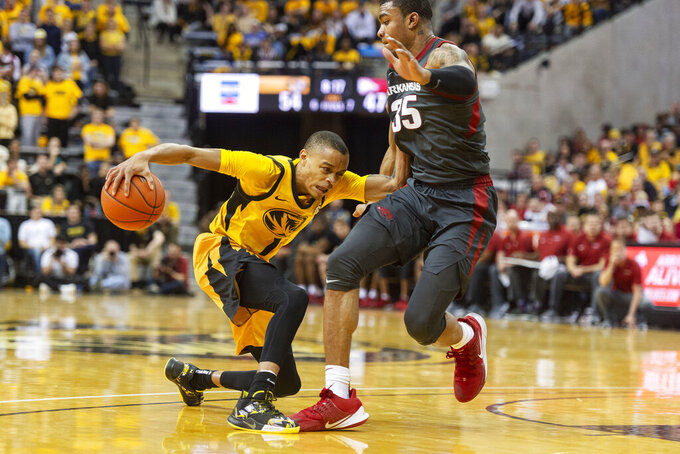 Missouri's Xavier Pinson, left, pushes past Arkansas' Reggie Chaney, right, during the second half of an NCAA college basketball game Saturday, Feb. 8, 2020, in Columbia, Mo. Missouri beat Arkansas 83-79 in overtime. (AP Photo/L.G. Patterson)
