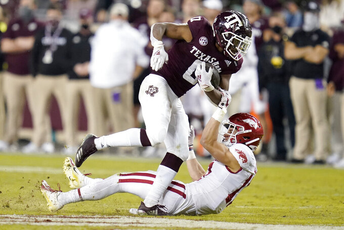 Texas A&M running back Ainias Smith (0) is tackled by Arkansas defensive back Hudson Clark (17) after knocking Clark over during a run in the second half of an NCAA college football game, Saturday, Oct. 31, 2020, in College Station, Texas. (AP Photo/Sam Craft)