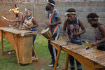 Marimba players in traditional Zulu dress play their instruments in the yard of a home in the Orange Farm Township south of Johannesburg, Wednesday, April 14, 2021.  Amid the classes in dancing and marimba music, a leader of the culture group praised Britain's Prince Philip, who died last week and whose Duke of Edinburgh Awards helped to fund the culture group's activities. (AP Photo/Denis Farrell)