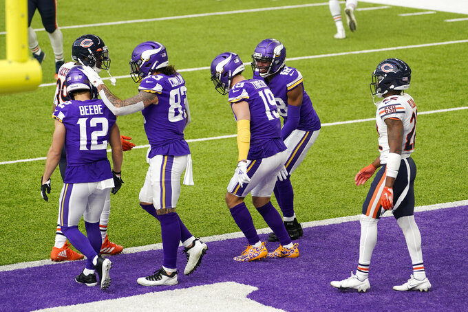 Minnesota Vikings wide receiver Adam Thielen (19) celebrates with teammates after catching a 3-yard touchdown pass during the first half of an NFL football game against the Chicago Bears, Sunday, Dec. 20, 2020, in Minneapolis. (AP Photo/Jim Mone)