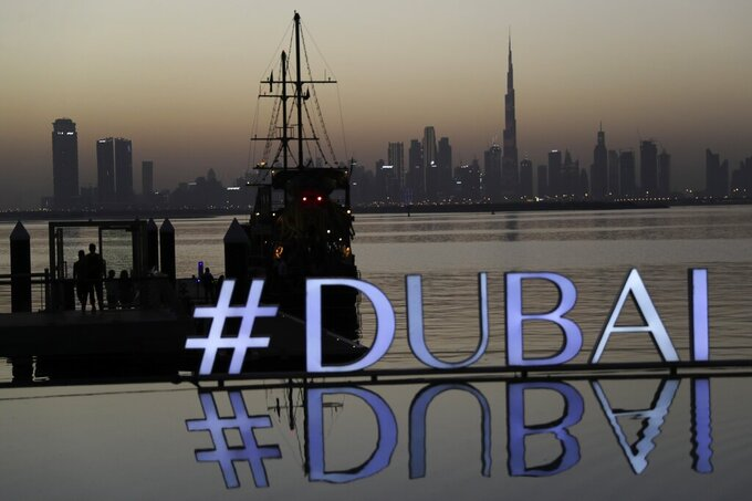 FILE - In this Jan. 29, 2021 file photo, people embark on a dinner dhow cruise after sunset with a view of the city skyline and a sign promoting Dubai, in Dubai, United Arab Emirates. Dubai's sovereign wealth fund announced Tuesday, June 22, 2021, a net loss of $5.1 billion over the past year, highlighting the toll that the coronavirus pandemic has wrought on the company's vast assets and the uncertainty around the emirate's post-pandemic recovery. (AP Photo/Kamran Jebreili, File)
