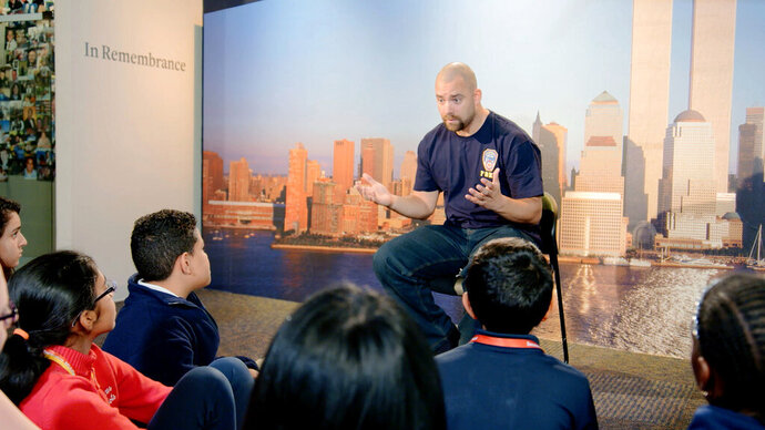 This image released by HBO shows a New York City Fireman speaking to children in a scene from the documentary