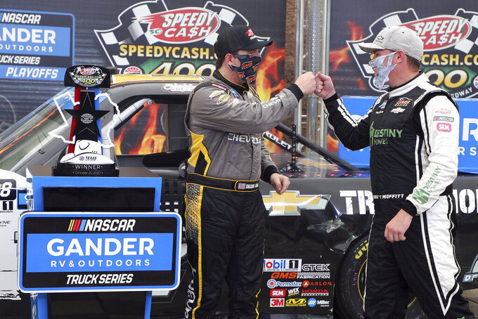NASCAR Texas Trucks Series driver Sheldon Creed, left, gets a fist bump from driver Brett Moffitt (23) as he celebrates in Victory Lane after winning an auto race at Texas Motor Speedway in Fort Worth, Texas, Sunday, Oct. 25, 2020. (AP Photo/Richard W. Rodriguez)