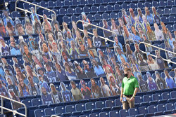 A man walks by seats filled by cardboard cutouts before an NFL football game between the Tennessee Titans and the Jacksonville Jaguars Sunday, Sept. 20, 2020, in Nashville, Tenn. (AP Photo/Mark Zaleski)