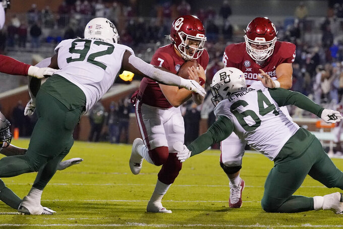 Oklahoma quarterback Spencer Rattler (7) carries the ball between Baylor defensive tackles Josh Landry (92) and Ryan Miller (64) in the first half of an NCAA college football game Saturday, Dec. 5, 2020, in Norman, Okla. (AP Photo/Sue Ogrocki)