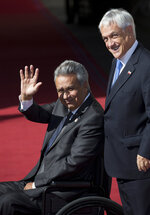 Ecuador's President Lenin Moreno, left, waves to journalists as he is received by Chile's President Sebastian Pinera, at  La Moneda presidential palace in Santiago, Chile, Friday, March 22, 2019. South American heads of state are meeting to discuss the development of a new regional political bloc called Prosur, the idea being to replace the Unasur, the current body that many describe as defunct. (AP Photo/Esteban Felix)